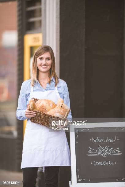 A female business owner stands outside her bakery and holds freshly-baked bread