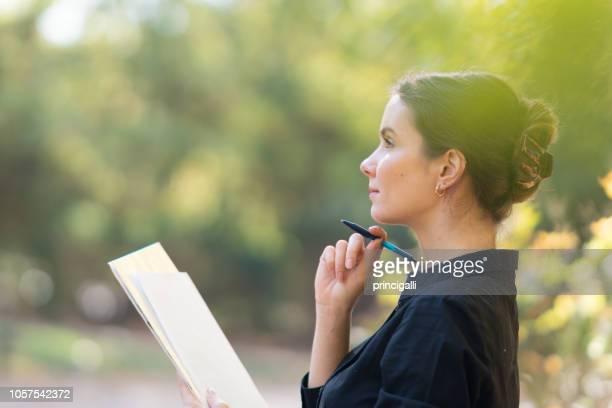 weibliche unternehmer oder student mit stift und papier im park - schreiben stock-fotos und bilder