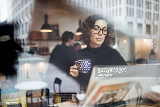 female business professional reading a newspaper in cafe - de media stockfoto's en -beelden