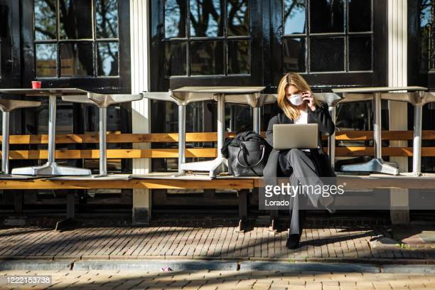 a female business woman wearing a face mask during viral outbreak - south holland stock pictures, royalty-free photos & images