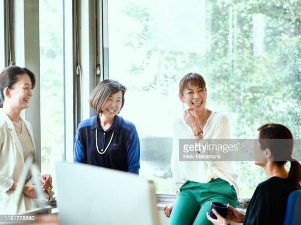 female businessman talking laughing with colleagues by the office window. - business ストックフォトと画像