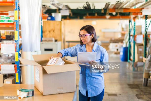 female businesswoman checking delivery in a small business - small business stock pictures, royalty-free photos & images