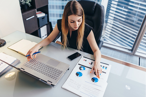 Female businesswoman readind financial report analyzing statistics pointing at pie chart working at her desk 1125578452
