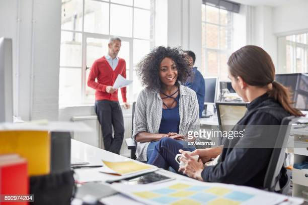 Female businesswoman talking with young male colleague at office