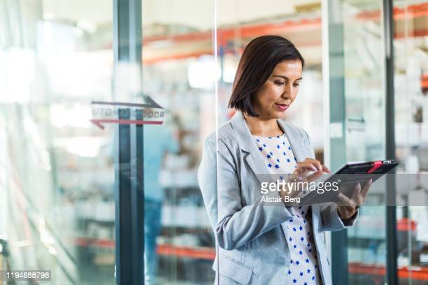 female businesswoman using tablet computer in a small business - business finance and industry stock pictures, royalty-free photos & images