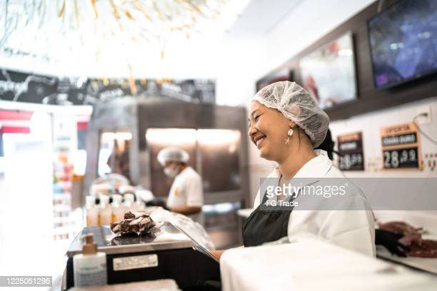 female butcher greeting customer at butcher's shop - market retail space stock pictures, royalty-free photos & images