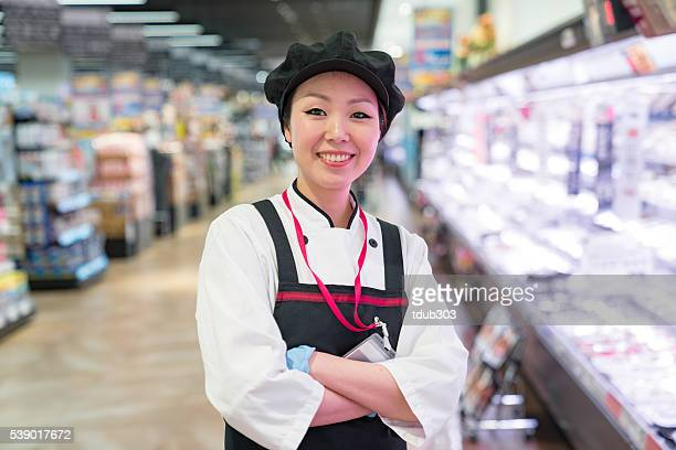 Female butcher in a supermarket meat department