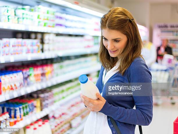 Female buying milk in supermarket