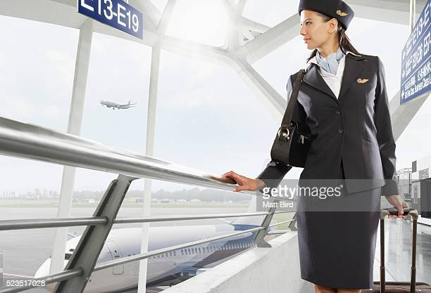 Female cabin crew member looking out of airport window