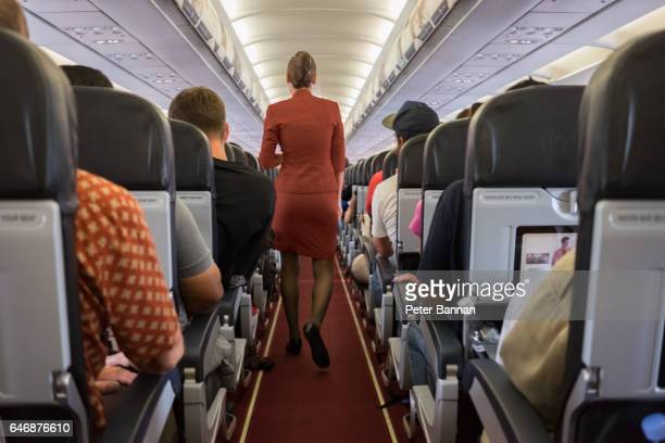Female cabin crew walks away down aircraft cabin isle