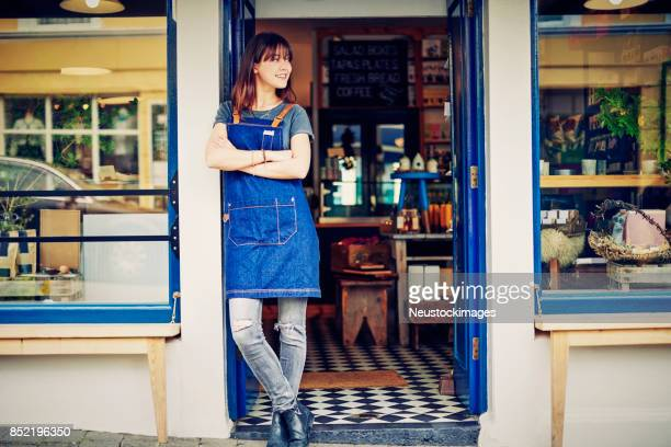 female cafe owner standing arms crossed in doorway - legs crossed at ankle stock pictures, royalty-free photos & images