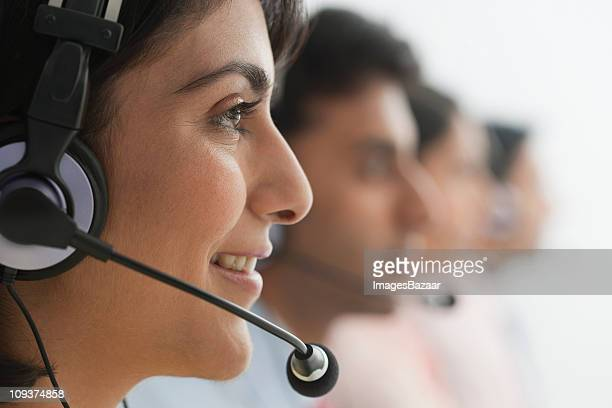 Female call centre worker wearing headset, colleagues in background