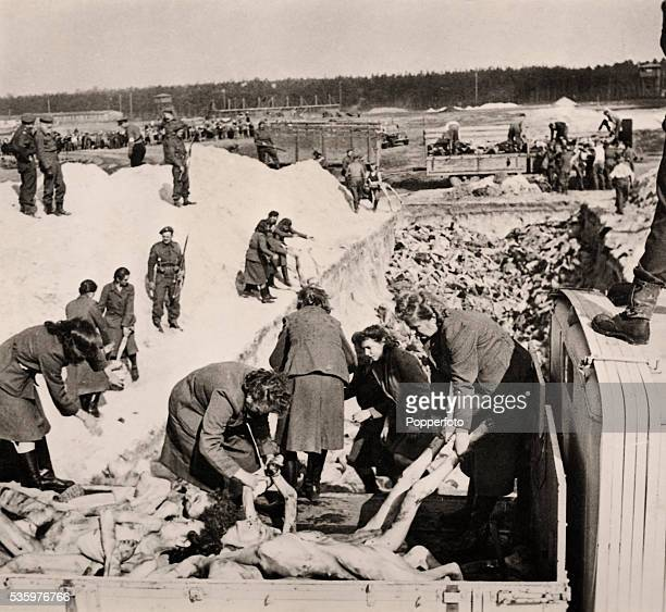 Female camp guards are forced to help with the burial of Jewish prisoners in mass graves at the Belsen Concentration camp which was liberated by the...