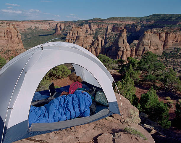 Female camper using laptop in tent, sunset