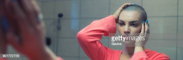 female cancer patient looking at herself in the mirror - psychiatric hospital stock pictures, royalty-free photos & images