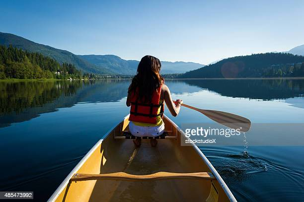 Female canoeing on a pristine lake