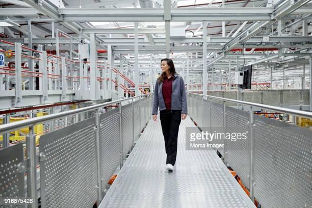 vrouwelijke auto ingenieur wandelen op verhoogde loopbrug - veiligheidshek stockfoto's en -beelden