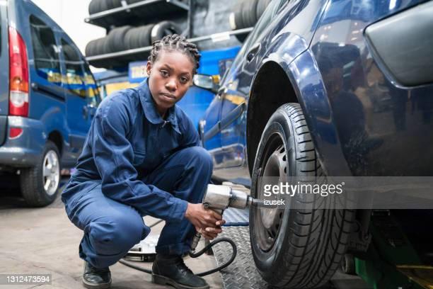 weibliche automechaniker wechselrad - izusek stock-fotos und bilder