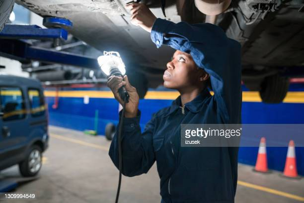 female car mechanic checking car chassis - izusek stock pictures, royalty-free photos & images
