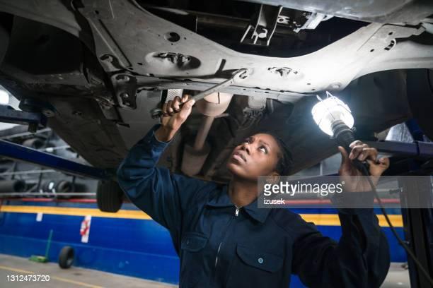 mecânico de carros feminino verificando chassis do carro - izusek - fotografias e filmes do acervo