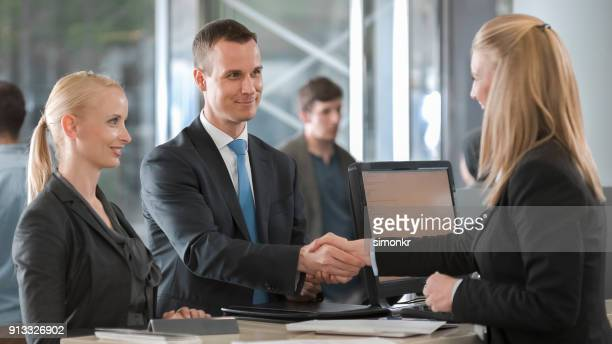 female car rental agent shaking hands with young couple and handing them key to rental car - cashier stock pictures, royalty-free photos & images