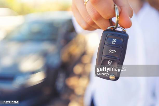 female car salesperson handing  over the new car keys - car key stock pictures, royalty-free photos & images