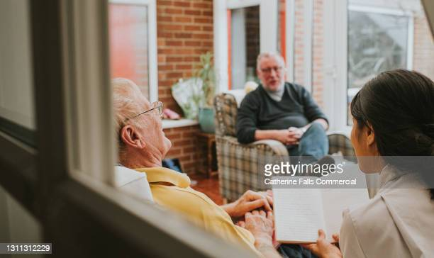 female care assistant sits beside an elderly male and reads to him - reading glasses stock pictures, royalty-free photos & images