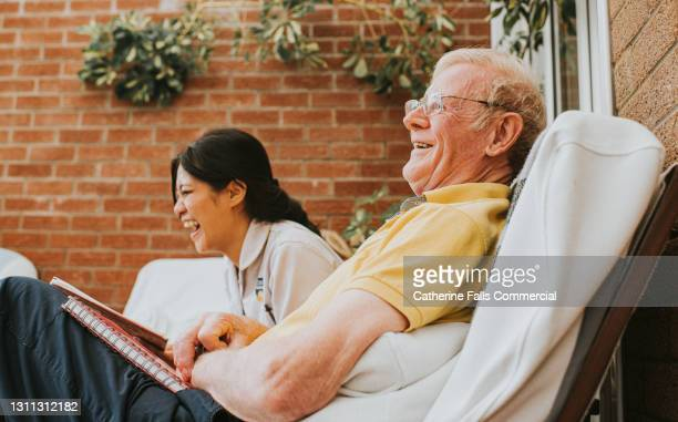 female care assistant sits beside an elderly male, they both laugh - reading glasses stock pictures, royalty-free photos & images