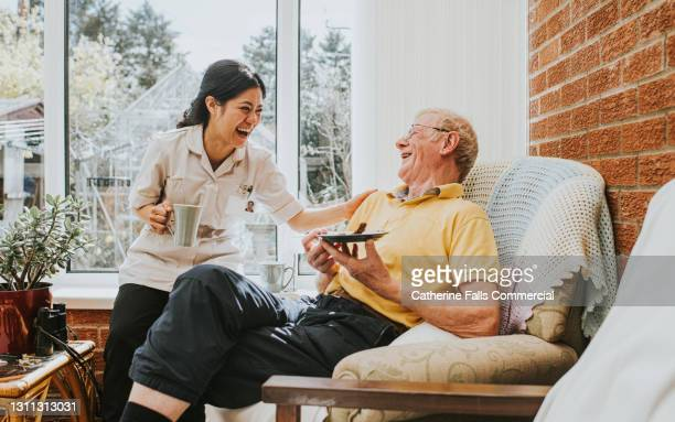 female care assistant spends some time with an elderly man in his home - care stock pictures, royalty-free photos & images