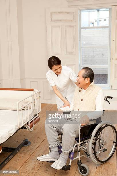 Female caregiver and senior man in wheelchair smiling face to face