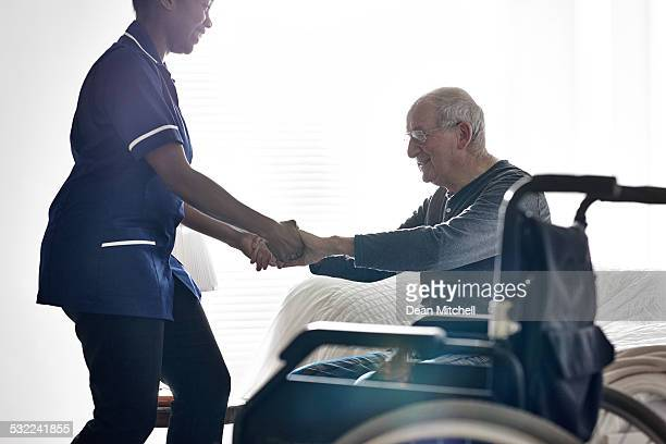 Female caregiver helping senior man get up from bed