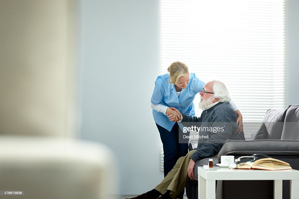 Female caregiver helping senior man get up from couch : Stock Photo