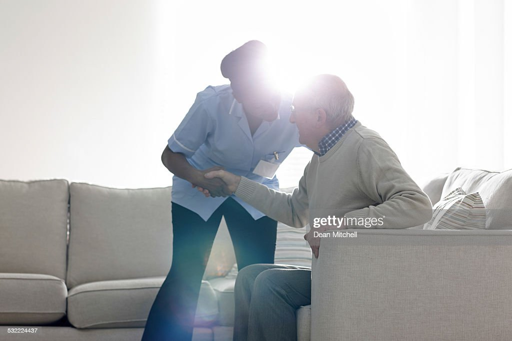Female caregiver helping senior man get up from sofa : Stock Photo