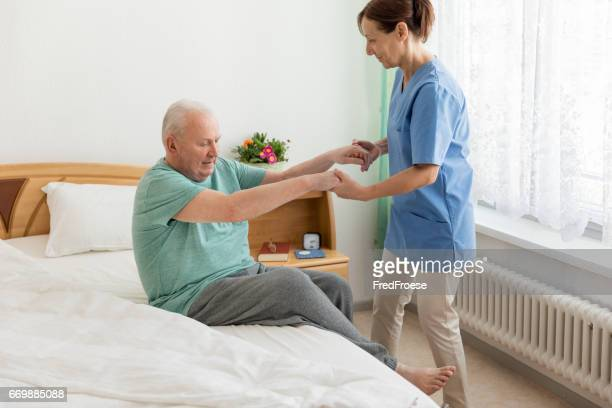 female caregiver helping senior man - nursing assistant stock pictures, royalty-free photos & images
