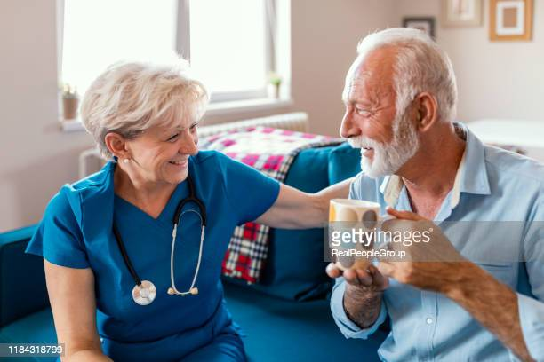 female caregiver serving afternoon tea to patien - hospice stock pictures, royalty-free photos & images