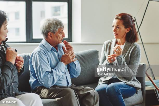 female caregiver visiting senior couple at retirement home - human body part stock pictures, royalty-free photos & images