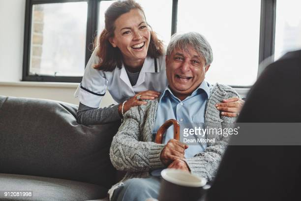 female carer enjoying with senior people at care home - janitorial services stock photos and pictures