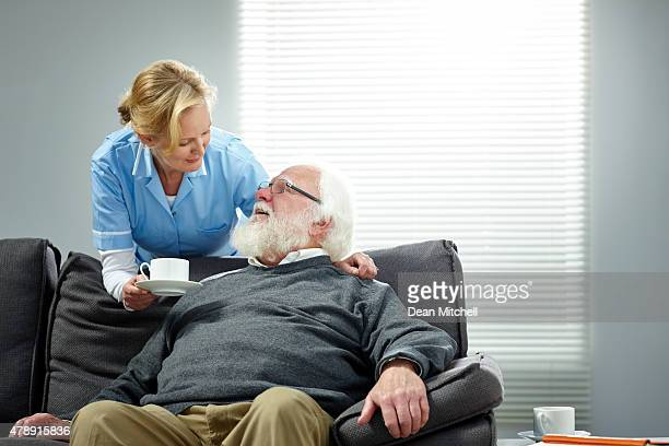 female carer giving coffee to senior man - woman sitting on man's lap stock pictures, royalty-free photos & images