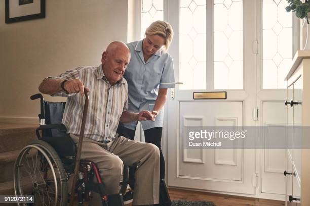 female carer helping disabled senior man to walk - patient safety stock pictures, royalty-free photos & images