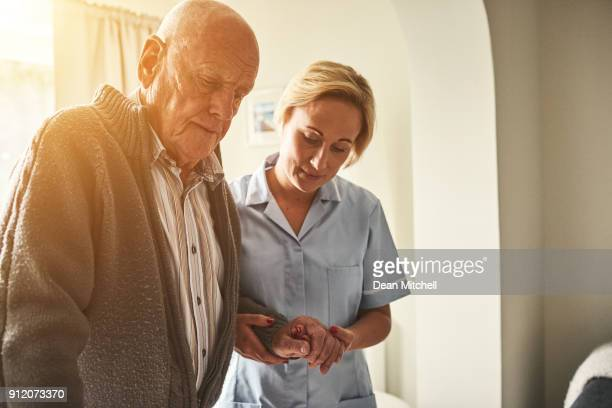 female carer helping patient to walk at home - walking cane stock photos and pictures