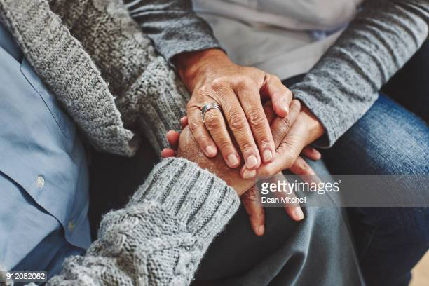 Female carer holding hands of senior man