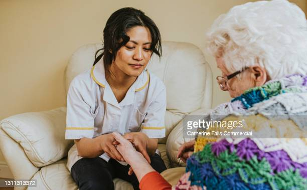 female carer holds an elderly woman's hand - charity and relief work stock pictures, royalty-free photos & images