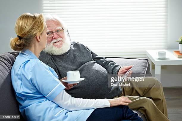 Weibliche Pflegekraft Sitzbereich mit alter Mann spricht