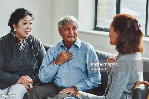 female carer treating senior couple - sign stock pictures, royalty-free photos & images