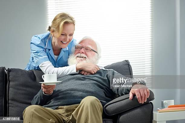 weibliche pflegekraft reisen mit alter mann sitzt auf sofa lächelnd - 50 54 jahre stock-fotos und bilder