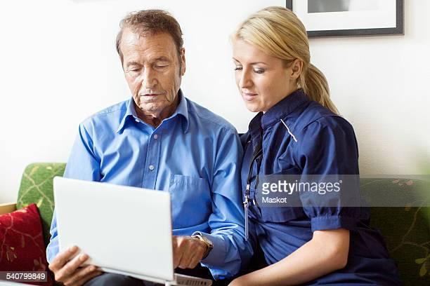 Female caretaker and senior man using laptop at nursing home