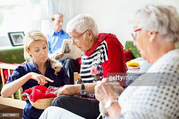 Female caretaker assisting senior women in knitting while man reading book in background at nursing home