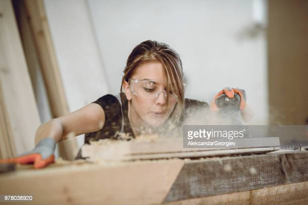 female carpenter blowing dust while sanding plank - carpenter stock pictures, royalty-free photos & images