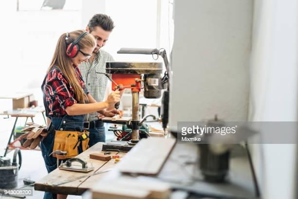 frau zimmermann bohren holzbrett in der werkstatt - unterschicht stereotypen stock-fotos und bilder