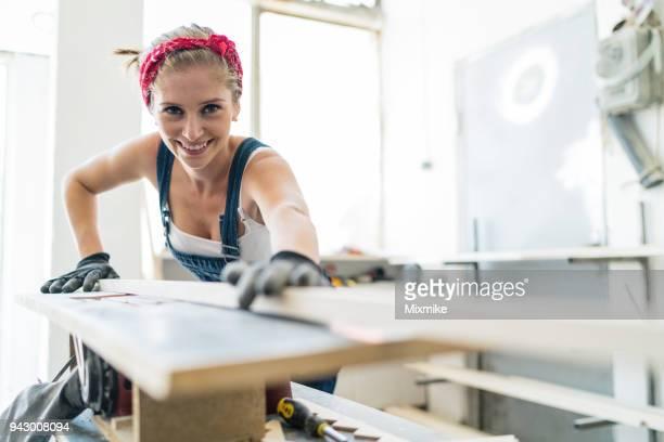 Frau Zimmermann Schleifen Holzbohle auf Schreinerei